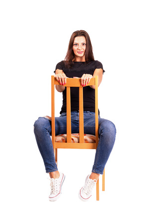 Woman sitting backwards on the chair posing looking at camera. Full body length isolated over white background.