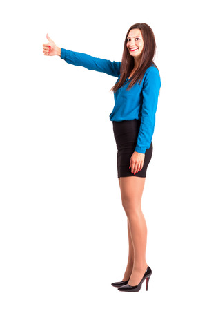 victory stand: Side view of business woman with thumbs up gesture looking at camera. Full body length isolated over white background.