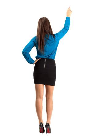 Achteraanzicht van lang haar brunette zakelijke vrouw die met potlood. Full body lengte geïsoleerd op een witte achtergrond.