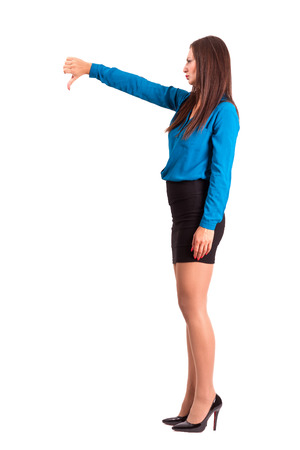 THUMBS DOWN: Angry business woman in skirt and high heels showing thumbs down. Side view. Full body length isolated over white background. Stock Photo