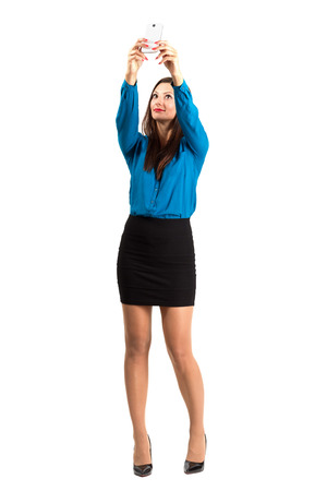 stockings heels: Business woman in high heels and skirt taking high angle selfie or self photo. Full body length isolated over white background.