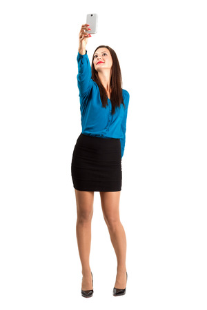 Business woman in high heels taking high angle selfie with one hand. Full body length isolated over white background. Stock Photo