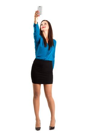 cuerpo completo: Mujer de negocios en tacones altos teniendo alta Autofoto ángulo con una mano. Encuadre de cuerpo entero sobre fondo blanco. Foto de archivo