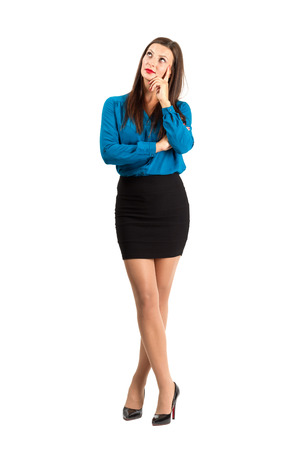 Pensive thinking business woman standing with crossed legs. Full body length isolated over white background. photo