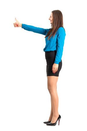Profile side view of business woman with thumbs up gesture. Full body length isolated over white background. photo