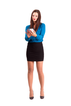 Brunette business woman using touch screen on her smart phone. Full body length isolated over white background. photo