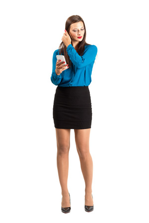 young woman legs up: Business woman checking her hair by looking on her mobile phone reflection or photo. Full body length isolated over white background. Stock Photo