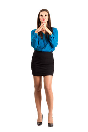 Deliberating young business woman with aligned fingers. Full body length isolated over white background. photo