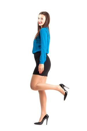 Het bedrijfs vrouw stellen met opgeheven been. Full body lengte geïsoleerd op een witte achtergrond. Stockfoto