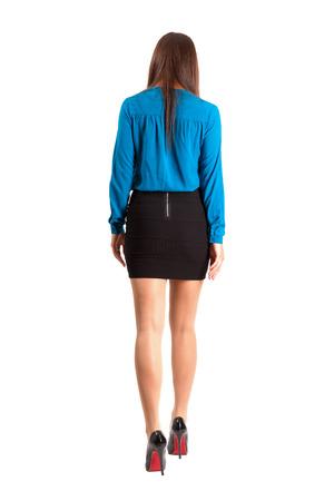 Long hair brunette woman in skirt and high heels walking away. Full body length isolated over white background.