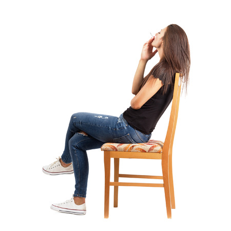 Side view of smoking casual woman sitting on chair. Full body length isolated over white background.
