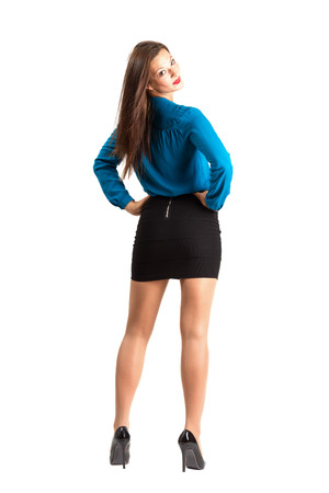 Standing business woman rear view looking at camera over the shoulder. Full body length isolated over white background. photo