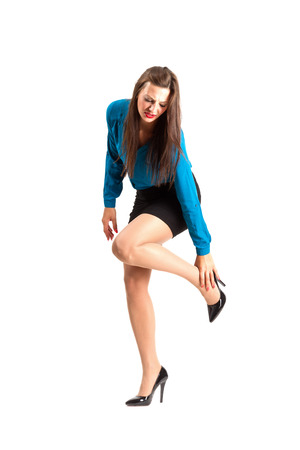 bent over: Business woman in stiletto holding her ankle. Full body length isolated over white background.