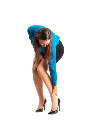 bent over: Business woman in high heels touching her ankle. Full body length isolated over white background.