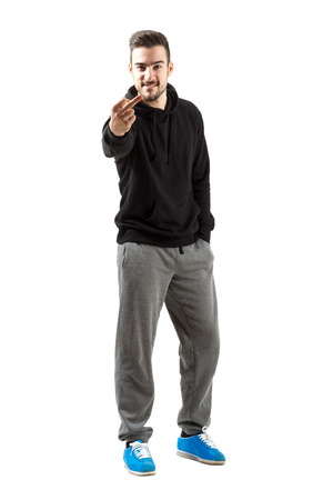 tracksuit: Young man in hoodie and sweatpants showing middle finger gesture. Full body length isolated over white background.