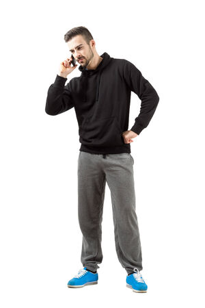 Serious young man in sportswear talking on mobile phone. Full body length isolated over white background. photo