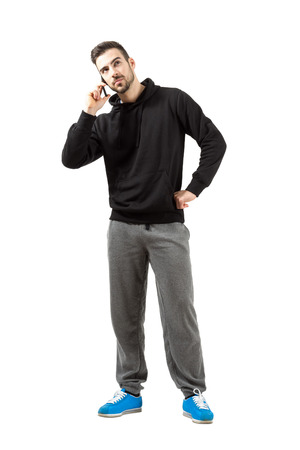 tracksuit: Young man in hood and sweatpants talking on mobile phone.  Full body length isolated over white background.