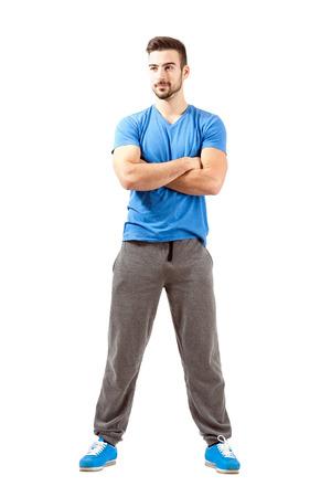 mani incrociate: Fiducioso giovane maschio in forma con le mani giunte guarda lontano. Lunghezza del corpo pieno isolato su sfondo bianco. Archivio Fotografico
