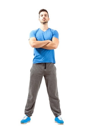 Serious confident fit guy posing with crossed hands and head back. Full body length isolated over white background. photo