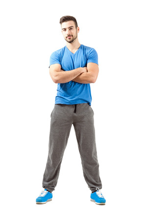 Young athlete with folded arms smiling looking at camera. Full body length isolated over white background. photo