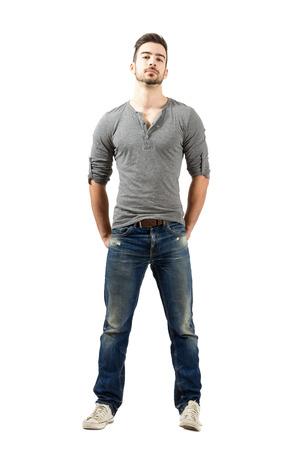 Jonge fit man in v-hals t-shirt, gescheurde jeans en sneakers staan met de handen in de achterzak. Full body lengte portret over een witte achtergrond.