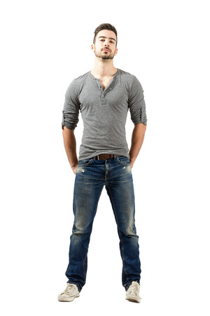 Young fit man in v-neck t-shirt, torn jeans and sneakers standing with hands in back pocket. Full body length portrait isolated over white background. Stock Photo