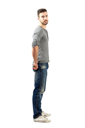 from side: Side view of young fit guy in jeans and sneakers looking at camera. Full body length portrait isolated over white background. Stock Photo