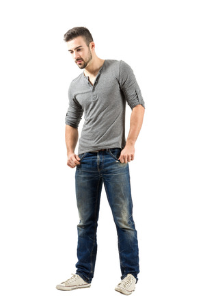 Young male standing looking down. Full body length portrait isolated over white background. Stockfoto