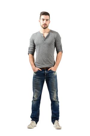 Jonge geschikte staande man met de handen in de zak. Full body lengte portret over een witte achtergrond.