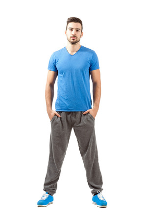 spread legs: Young proud confident fit male in sportswear. Full body length portrait isolated over white background.