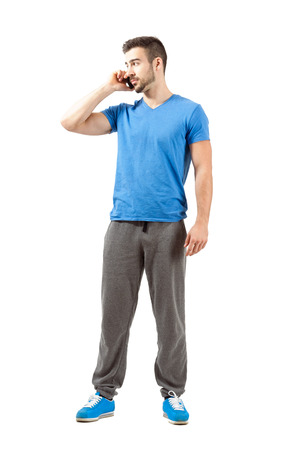 Young fit male in sweatpants talking on the phone looking away. Full body length portrait isolated over white background.