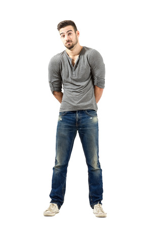 v neck: Confused young man with raised shoulders. Full body length isolated over white background. Stock Photo