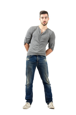 v neck: Confused young man with hand clasped on his back. Full body length isolated over white background.