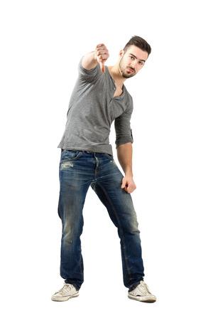 cuerpo entero: Hombre joven infeliz que muestran los pulgares hacia abajo gesto. Encuadre de cuerpo entero sobre fondo blanco.