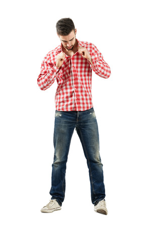 Trendy modern guy buttoning plaid shirt. Full body length portrait isolated over white background. photo