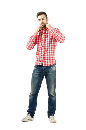 Fashionable man arranging collar on his plaid shirt looking at camera. Full body length portrait isolated over white background.