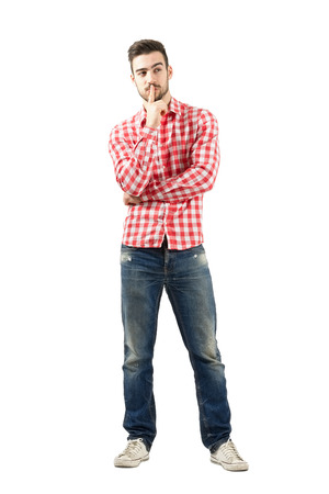Thinking young guy with finger over his mouth. Full body length portrait isolated over white background.