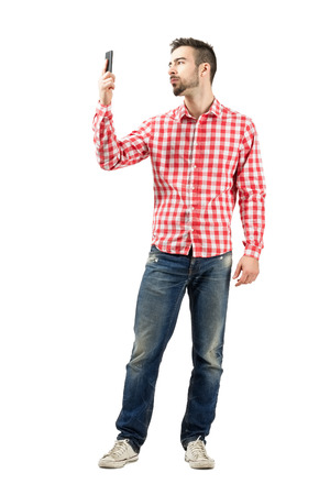 Man in plaid shirt checking his smart phone. Full body length portrait isolated over white background.