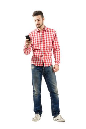 Jonge casual man met behulp van slimme telefoon. Full body lengte portret geïsoleerd op een witte achtergrond. Stockfoto