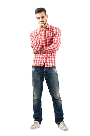 man looking down: Worried young man in plaid shirt. Full body length portrait isolated over white background. Stock Photo
