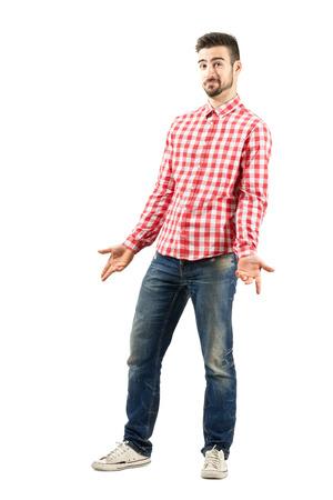 expresion corporal: Hombre joven confundido seguro en camisa a cuadros encogimiento. Encuadre de cuerpo entero sobre fondo blanco. Foto de archivo