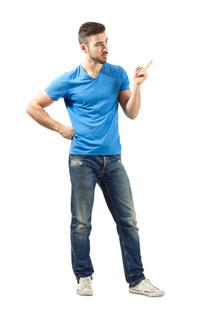 Young man solving problems with pointed index finger. Full body length isolated over white background. Reklamní fotografie