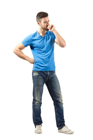 Young man in blue t-shirt thinking looking down. Full body length isolated over white background. 免版税图像