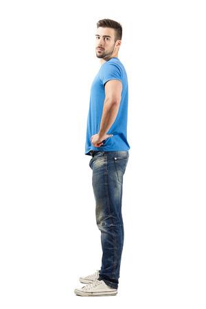 Junger Mann, der Mode-Modell stand mit verschränkten Armen in die Hüften Seitenansicht. Ganzkörper-Länge über weißem Hintergrund.