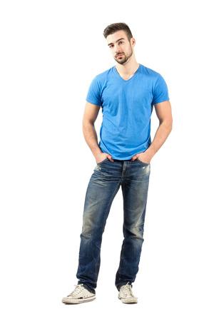 in jeans: Modelo de moda joven posando con las manos en los bolsillos. Encuadre de cuerpo entero sobre fondo blanco. Foto de archivo