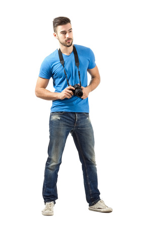 hang body: Young man standing with digital camera around neck. Full body length portrait isolated over white background.