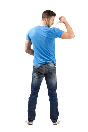 Young casual man rear view pointing with thumb on back of his shirt. Full body length portrait isolated over white background. Standard-Bild