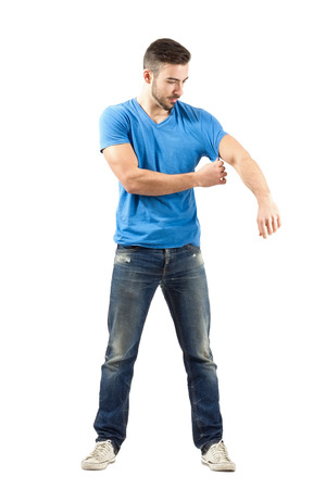 Young man fashion model taking off his shirt while holding sleeve. Full body length portrait isolated over white background. Stock Photo