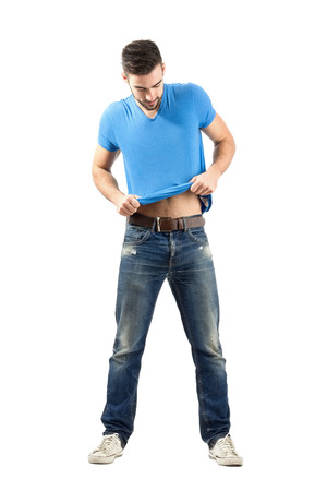 put: Young man fashion model putting on his t-shirt. Full body length portrait isolated over white background.