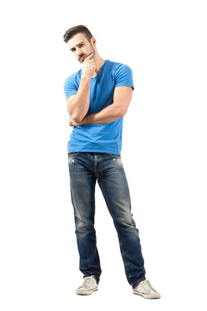 suspiciously: Doubtful young man looking at camera suspiciously. Full body length portrait isolated over white background. Stock Photo